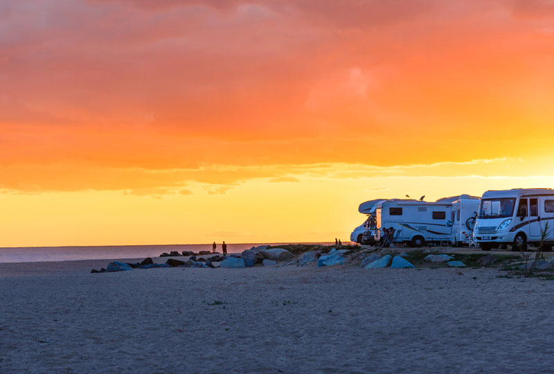 two people out on the beach during sunset with their motorhomes parked out on the side