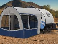 White and blue Forest River R-Pod travel trailer  with expanded canopy parked on sunny desert plain.